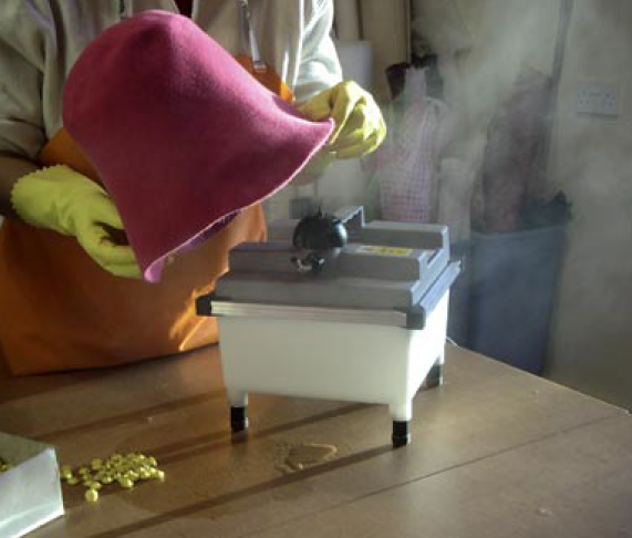 Making hats, steaming the felt.